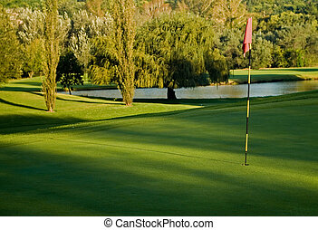 Golf green, flag and water hazard