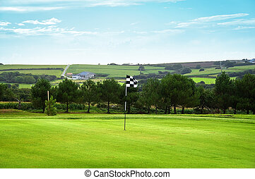 Golf green with a checkered flag, the countryside in background