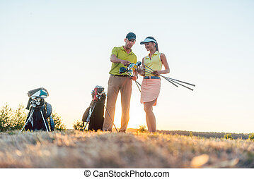 Golf instructor teaching a young woman how to use different golf clubs
