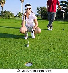 golf, mujer joven, mirar, y, apuntar, el, agujero