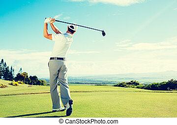 Golfer Hitting Golf Shot with Club on Beautiful Golf Course...