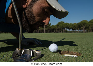 golf player blowing ball in hole