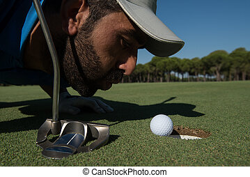 golf player blowing ball in hole. concept of cheating and...