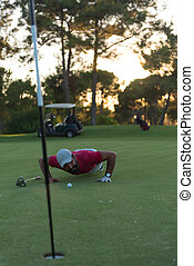golf player blowing ball in hole with sunset in background