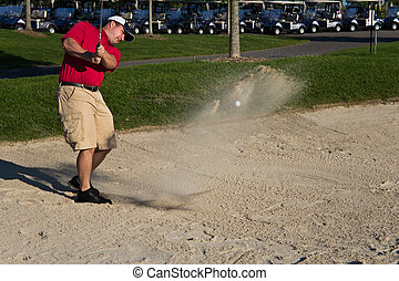 Golf player hitting the ball from the sand bunker