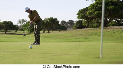Caucasian male golfer standing on a golf course wearing a cap and golf clothes playing a game, swinging a golf club and hitting the ball towards the hole, marked with a flagstick in the foreground