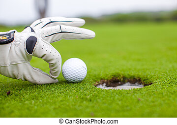 Golf player man pushing golfball into the hole - Golf player...