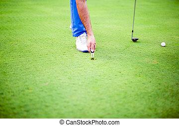 Golf player repairing divot on a green grass surface