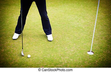 Golf player training putting ball on green