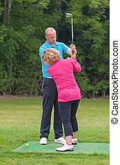 Golf pro correcting a lady golfers grip - A lady golfer...