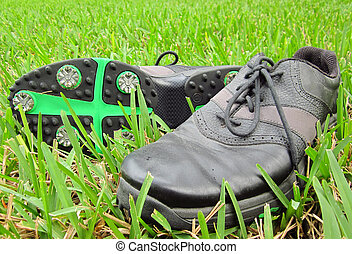 A pair of black golf shoes in the grass