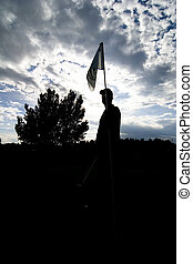 Silhouette of a golfer standing at the hole