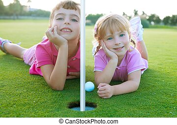 Golf two sister girls relaxed lying near green hole with ball