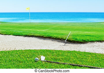 Golf stick and ball on grass against the sea. Rake near the sand.