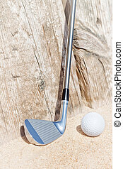 Golf stick and ball on the sand. Close-up.
