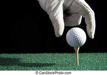 Golfball drop - Gloved hand putting a golf ball on a tee....