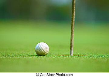 golfball on green - golfball close to hole