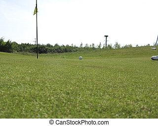 Golfball on green near hole