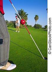 golfen, frau, setzen, gol, kugel, und, mann, hält, fahne