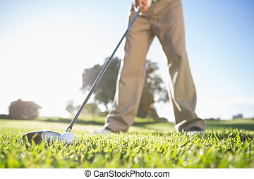 Golfer about to hit golf ball