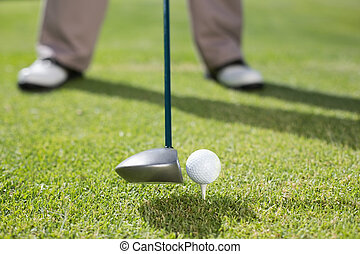 Golfer about to tee off on a sunny day at the golf course