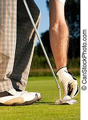 Golfer adjusting golf ball