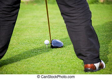 golfer adresses golf ball on tee
