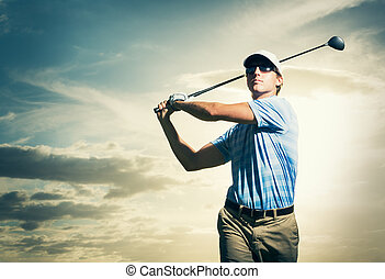 Golfer at sunset, Man swinging golf club with dramatic ...