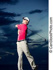 Golfer at sunset, Man swinging golf club with dramatic...