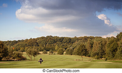 Golfer carrying a golf bag