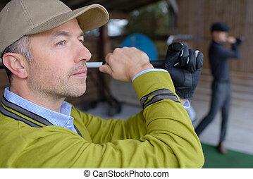 golfer choosing golf club on retail shop