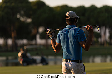 golfer from back at course looking to hole in distance - ...