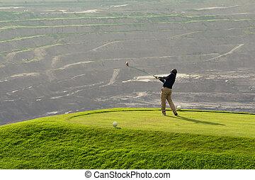 Golfer Hitting Ball with Club on Beatuiful Golf Course