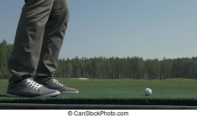 Golfer Hitting Ball with Club on Beautiful Golf Course. Golfer hits an fairway shot towards the club house. Man hitting driver on a golf course in the sun. Professional male golf player