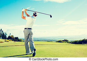 Golfer Hitting Golf Shot with Club on Beautiful Golf Course...