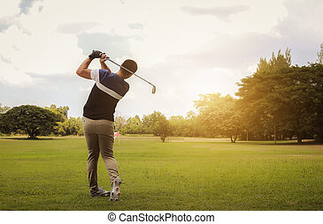 Golfer hitting golf shot with club on course at evening time.