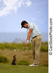 Golfer hitting iron shot from fairway
