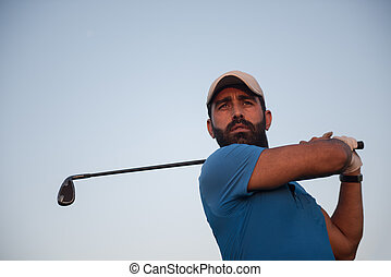 golfer hitting long shot with driver on course at beautiful...