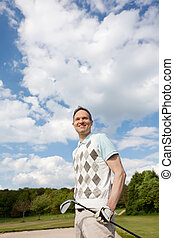 Golfer Holding Club While Looking Away Against Cloudy Sky