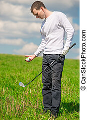 Golfer in full length on the field with balls and a golf club