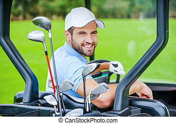 Golfer in golf cart. Rear view of young happy male golfer...