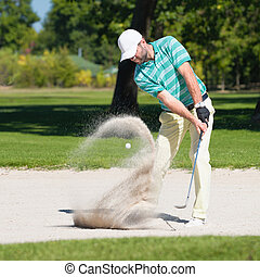 Golfer in sand trap - Golfer hits the ball out of sand trap....