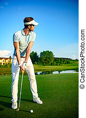 Golfer on putting green - Perfecting his putt. Golfer teeing...