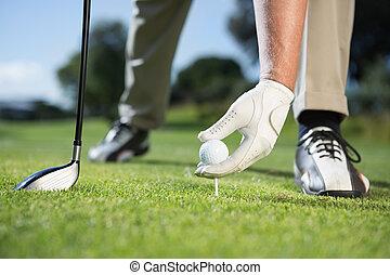 Golfer placing golf ball on tee
