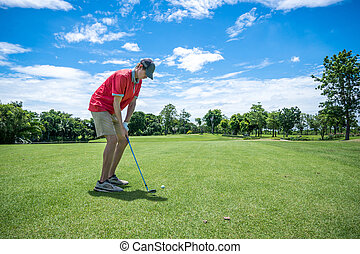 golfer playing golf with golf club on fairway