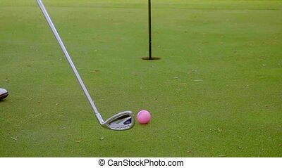 Golfer preparing to sink a putt at the hole with a colorful...