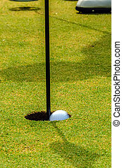 golfer putting a golf ball in to hole