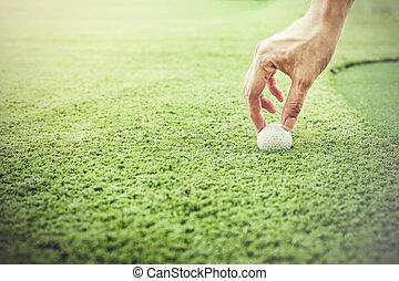 Golfer putting a golf ball onto green grass field - vintage aesthetic tone