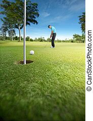 golfer putting at golf course, shallow depth of field