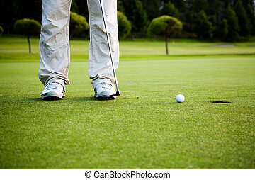 Golfer putting - Male golfer putting a golf ball in to hole